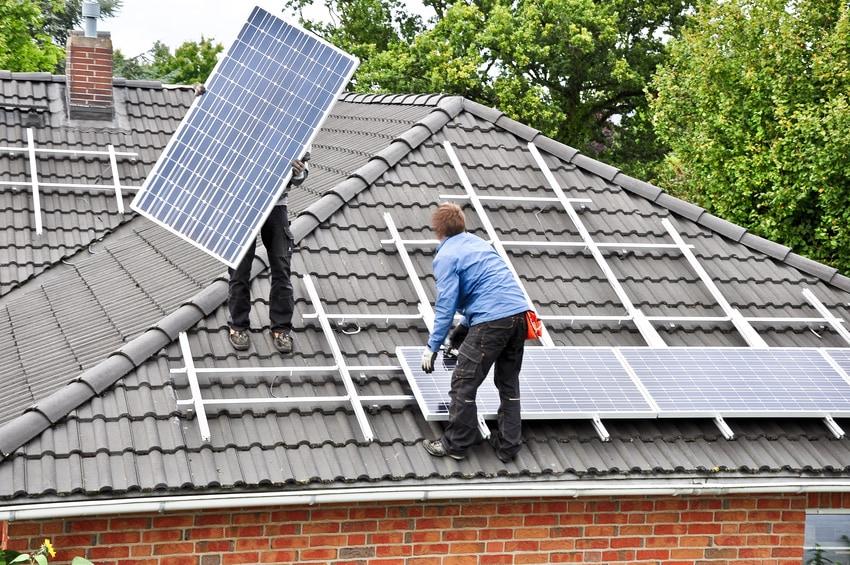 Zwei Personen installieren Photovoltaikmodule auf einem Dach