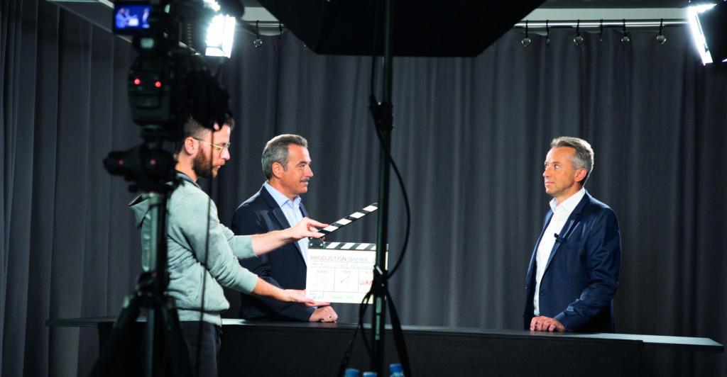 Rainer Breineßl und zwei weitere Personen auf einem Filmsetvor schwarzem Hintergrund