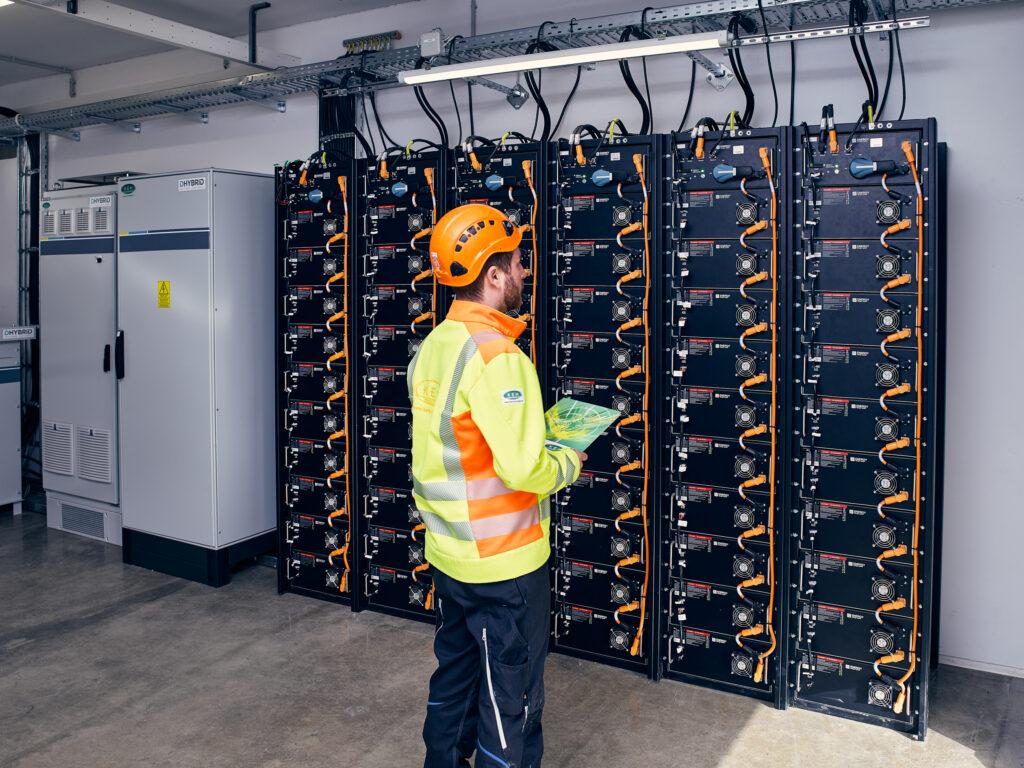 Mann vor einem Batteriespeicher