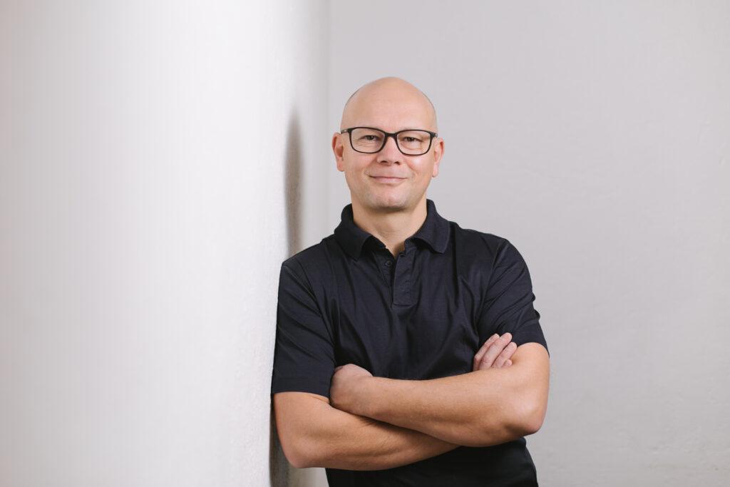 Mann mit Brille und schwarzenPolo-Shirt an Wand gelehnt.
